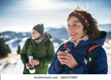 Senior couple hikers in snow-covered winter nature, drinking hot tea.