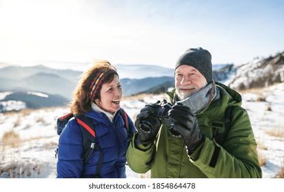 Senior couple hikers using binoculars in snow-covered winter nature.