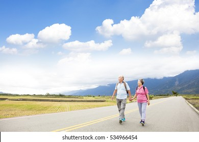 senior couple hiking on the country road