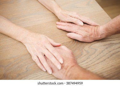 Senior couple holding hands on table