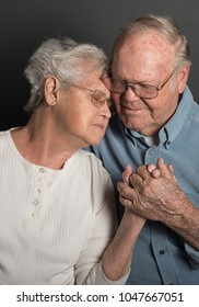 Senior couple holding hands in a tender loving embrace in monochrome, both wearing glasses, man unshaven