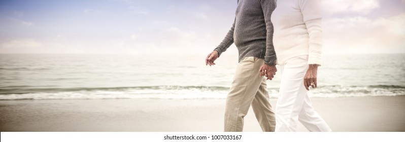 Senior couple holding hands and walking on the beach happily