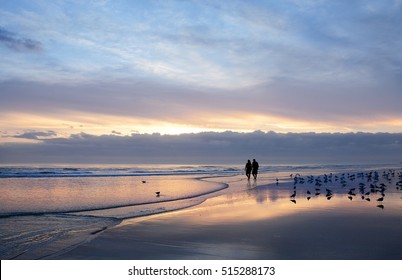 Senior couple holding hands walking on beautiful beach at sunrise. Sun reflected on the beach. Daytona Beach, Florida, USA.