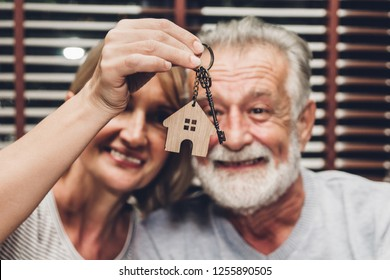 Senior couple holding key together sitting on sofa in living room from new house.Retirement couple and real estate concept
