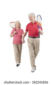 Senior couple holding tennis rackets