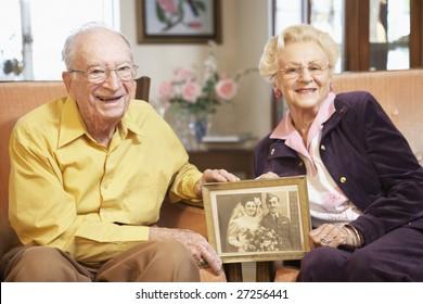 Senior couple holding wedding photo