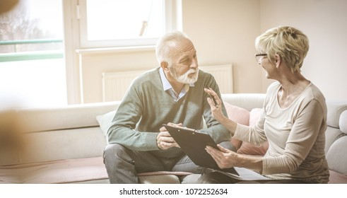 Senior couple at home with document and contractor.
