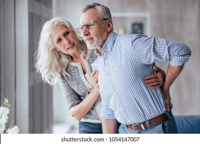 Senior couple at home. Handsome old man is having back pain and his attractive old woman supports him.