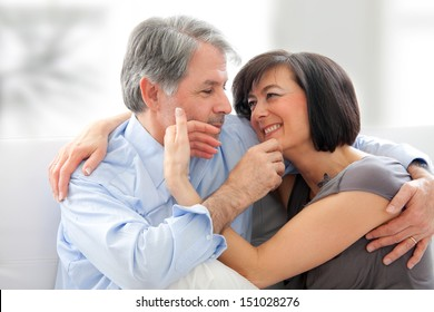senior couple at home on sofa. They caress each other tenderly face. He is gray-haired. It is brunette