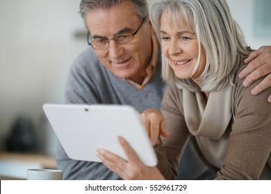 Senior couple at home using digital tablet