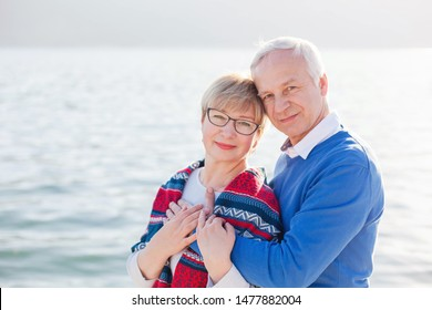 Senior couple is hugging and embracing at sea beach outdoor. Portrait of happy man and woman enjoying retirement and life. Concept of wellbeing, happiness, male and female health, precious moments.
