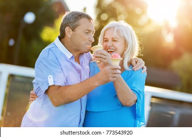 Senior couple hugging and laughing together, eating ice cream. Mature love.