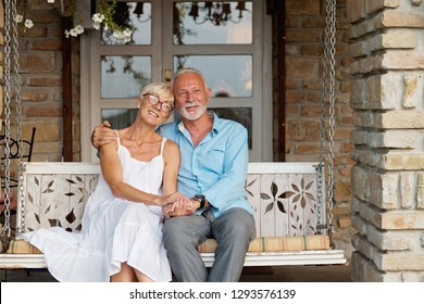 Senior couple hugging outdoors, smiling, in love