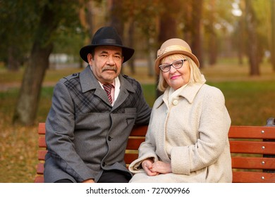 Senior couple, husband and wife, embracing each other lovingly in autumn park