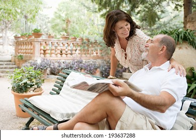 Senior couple husband and wife having a conversation and enjoying a holiday in a luxury hotel garden during a sunny day with the man reading a newspaper. Mature people lifestyle and retirement.