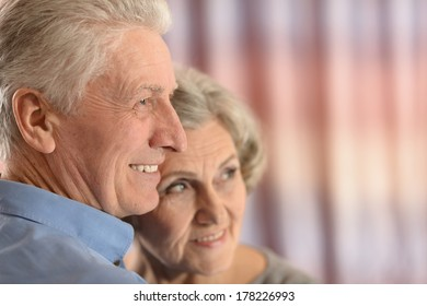 Senior couple isolated on colored background looking at something