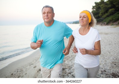 Senior couple jogging on the coast