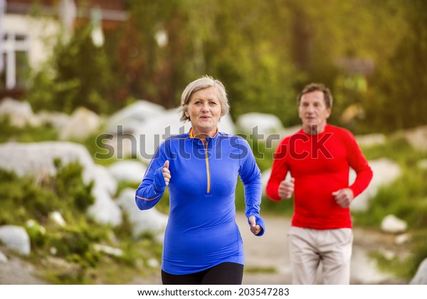 Senior couple jogging round the tarn in beautiful mountains, hills and hotel in background