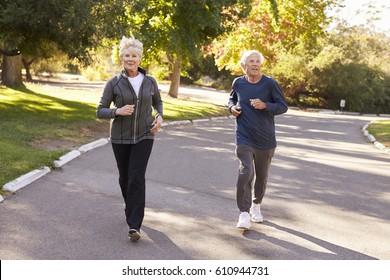 Senior Couple Jogging Through Park