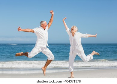 Senior couple jumping at the beach on a sunny day