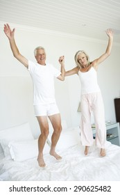 Senior Couple Jumping On Bed