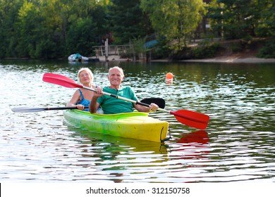 Senior couple kayaking on the river. Healthy elders enjoying summer day outdoors. Sportive people having fun at the nature. Active retirement concept.