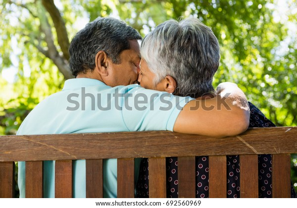 Senior couple kissing at the park on a sunny day