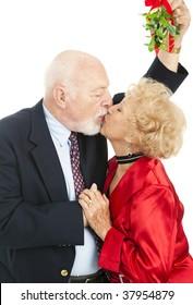 Senior couple kissing under the Christmas mistletoe.  White background.