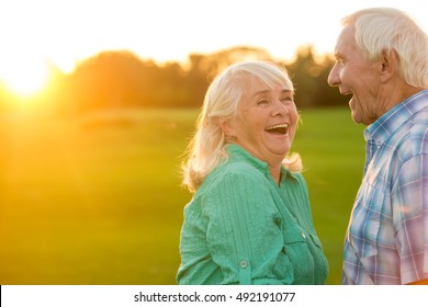Senior couple laughing. Man and woman outdoors. Sense of humour. Old funny jokes.