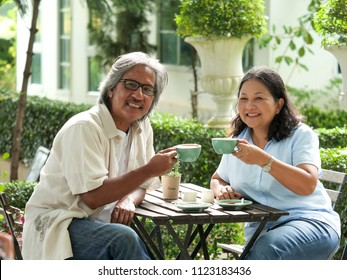 Senior couple laughing while drinking coffee in home garden.