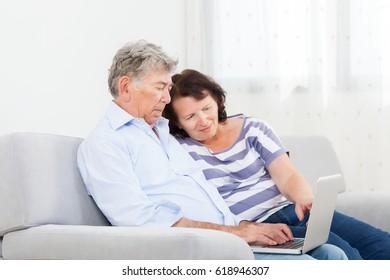 Senior couple laughing while using laptop