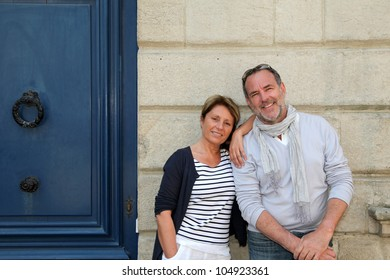 Senior couple leaning on wall in city
