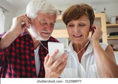 Senior couple listening to music on smartphone in kitchen