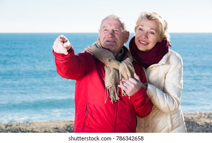 Senior couple looking at sky while taking walk by sea