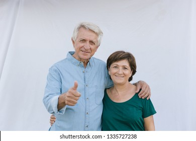 Senior couple looking and smiling with thumbs up