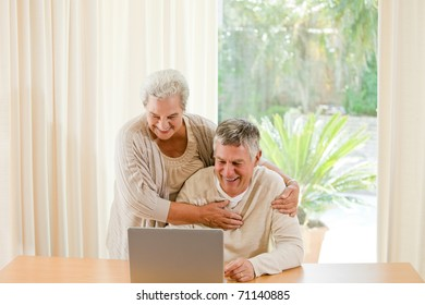 Senior couple looking at their laptop at home