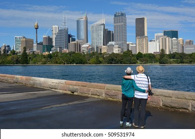 Senior Couple looks at Sydney Central Business District skyline as view from the Royal Botanic Gardens in Sydney New South Wales, Australia