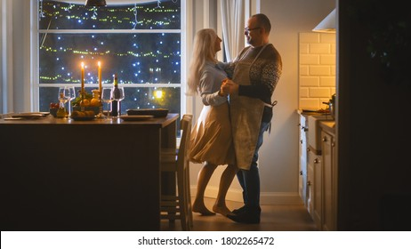 Senior Couple in Love Have Romantic Evening, Dancing in the Dining Room, Celebrating Anniversary. Portrait of a Happy Elderly Husband and Wife Have Lovely Evening with Festive Table in Cozy Kitchen