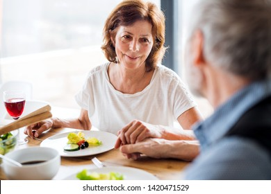 Senior couple in love having lunch indoors at home, holding hands.