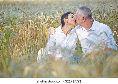 Senior couple in love kissing in a wheat field