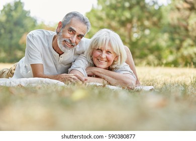 Senior couple in love lay happy on the gras in summer