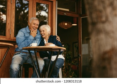 Senior couple in love sitting in cafe talking and having fun. Happy retirement couple relaxing at coffee shop.
