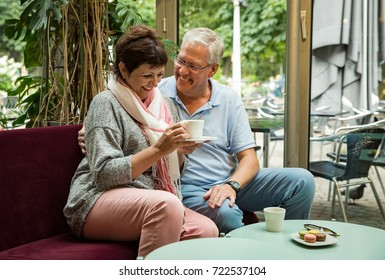 Senior couple in love sitting in cafe, drinking coffee, talking, laughing and having fun. Happy people in retirement concept.