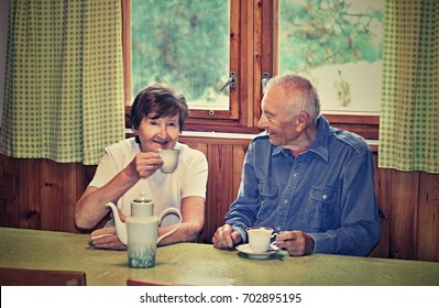 Senior couple in love sitting at the table in the dinning room and drinking tea. Concept of active elderly people during retirement. Everyday joy lifestyle without age limitation.