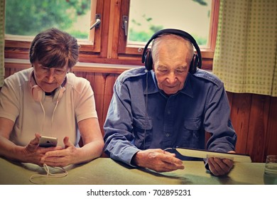 Senior couple in love sitting at the table in the dinning room and listening to music. Concept of active elderly people during retirement. Everyday joy lifestyle without age limitation.