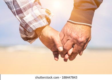 Senior couple in love walking at the beach holding hands in a romantic sunny day - Concept of love and family union