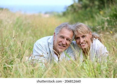 Senior couple lying down in country field