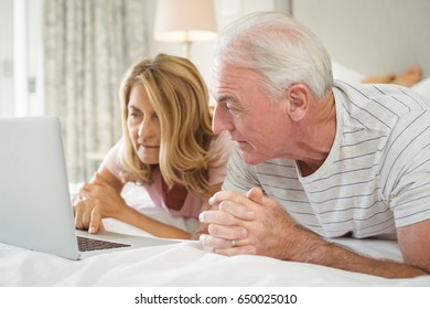 Senior couple lying on bed and using laptop in bed room
