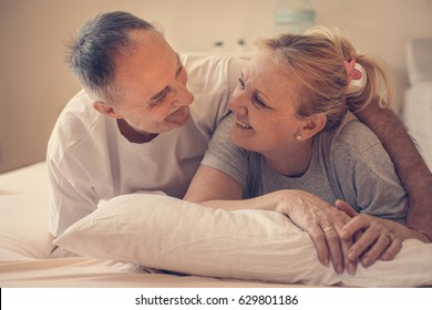 Senior couple lying together in bed and looking each other. Senior man hugging his wife.