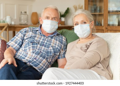 Senior couple in medical protective masks from coronavirus pandemic spread sitting on couch. Elderly man and female in face covers from covid-19 virus, staying at home. Healthcare and epidemic concept